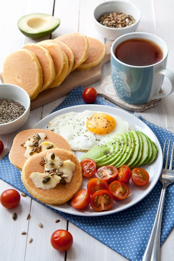 Corn pancakes breakfast plate - quick savory pancakes, delicious with butter, toasted seeds, served with an egg, avocado, and cherry tomatoes.