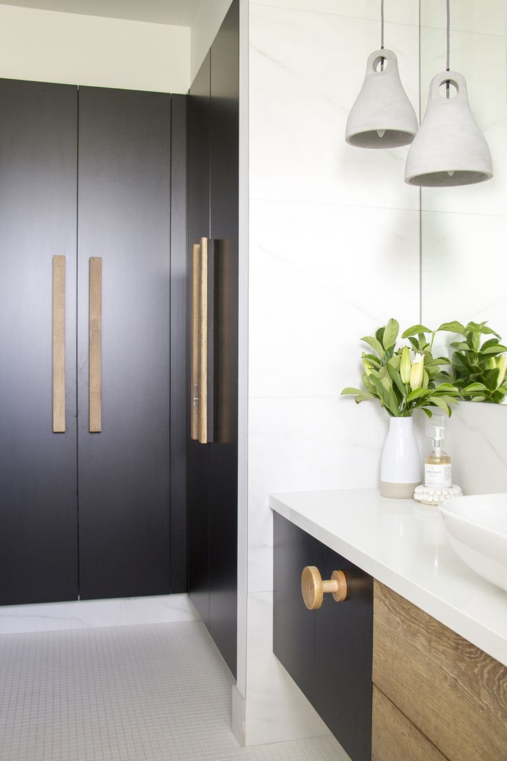 Interior Design by Mandie Wright of Tailored Space Interiors. Photography by Tanika Blair. Modern Sanctuary. Bathroom. Modern Bathroom. White and Black Bathroom. Bathroom Inspiration. Marble Walls. Wooden Knobs. Wooden Pulls. Cement Pendant Lighting. Bathroom Lighting. Bathroom Pendants.