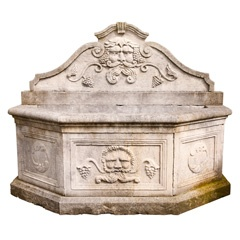 A large Italian carved limestone wall fountain