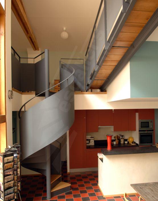 Escalier intérieur hélicoïdal métal et bois pour une décoration vintage. Rampe voile en tôle roulée