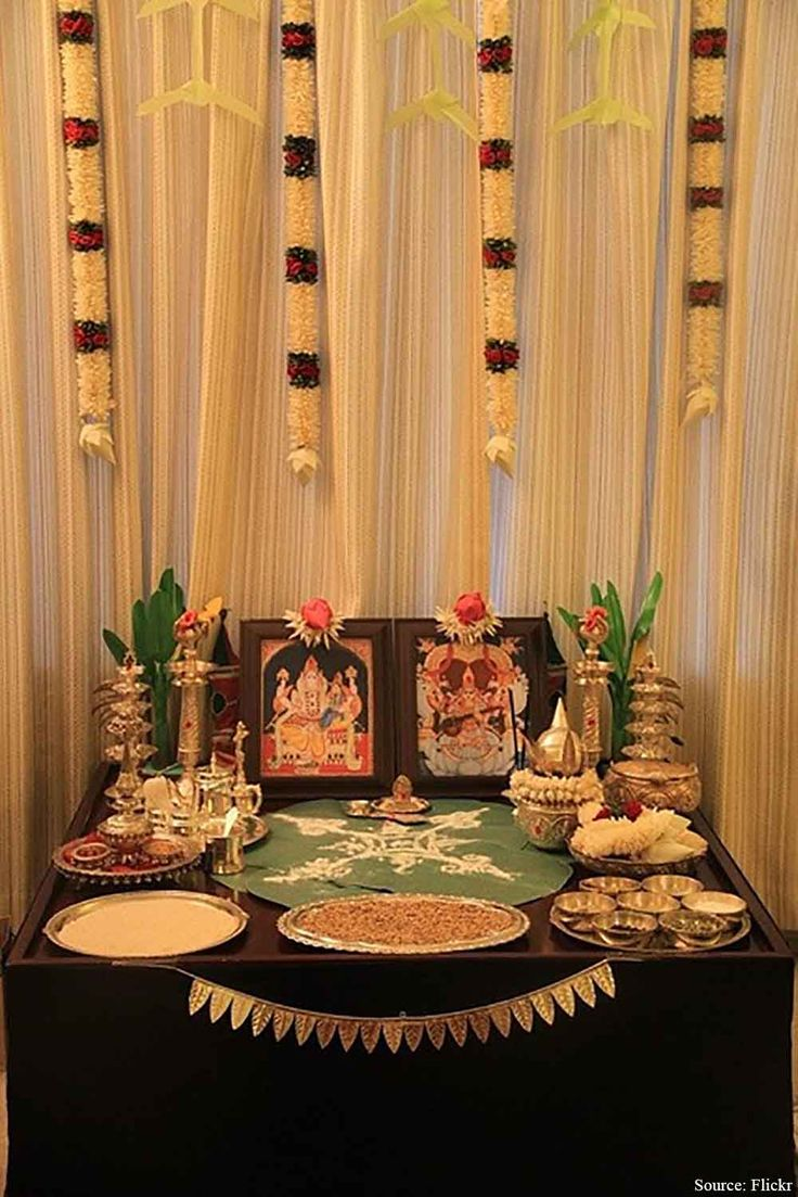 The broad wooden platform/table adorned with all the necessary ingredient or Diwali Puja. The metallic accents in the form of an urn, Puja Thali, Bowls, Diya Plate, Candle holders and much more placed om a huge Paan-Patta are softened by the Flower decoration on white drapery.