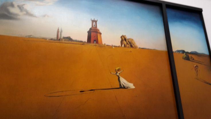 Dit is een schilderij van de kunstenaar Salvador Dalí. De titel van het schilderij is 'landschap met het touwtje springende meisje'. Het komt uit de periode het Surrealisme. Het touwtje springende meisje symboliseert een gelukkige jeugdherinnering. Ook zie je dat meisje in de klok van de kerk. De figuren rechts zouden Salvador en zijn overleden broer kunnen zijn. Het is gemaakt in 1936 en komt uit de collectie moderne kunst.