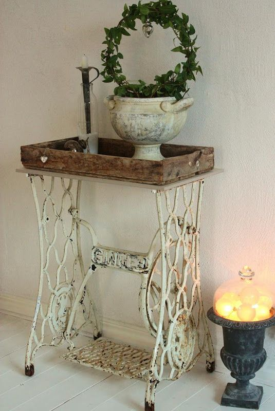 Antique Singer cast iron sewing table base used as plant trolley w/ vintage wooden tray on top.
