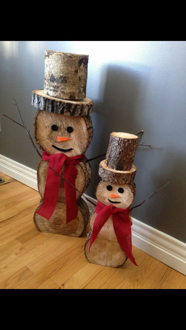little snowmen made out of cuts of logs.