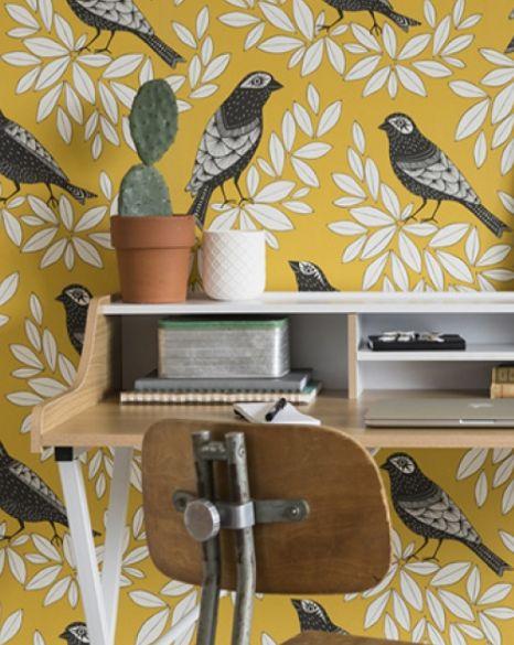Des oiseaux noirs et blancs ont élu domicile à travers un branchage sur fond jaune moutarde. Papier peint intissé, Songbird, collection Five Lands, MissPrint chez Au fil des Couleurs