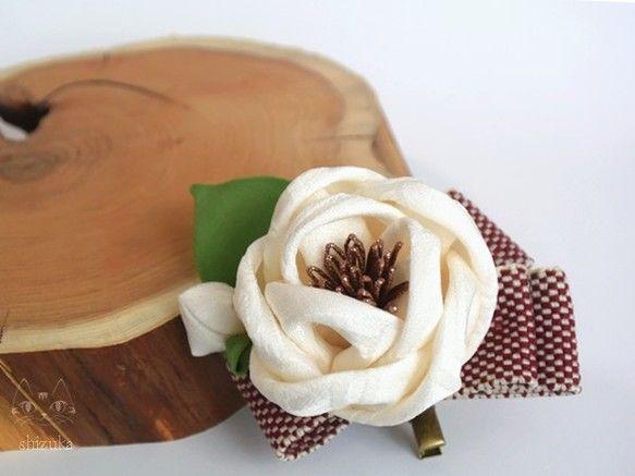 【サイズ】  横:7cm × 縦:6.5cm         椿:5.5cm 〔直径〕 【素 材】  正絹、着物生地、コサージュクリップピン etc...       ✄ - - - - - - - - - - - - - - - - - - - - - - - - - - - - - -ころんっと丸い淡いクリーム色の椿に、葉っぱと蕾、臙脂色の市松柄リボンを添えた、2wayクリップピンです。大正浪漫なレトロ雰囲気ただようお品です✧クリップとブローチが付いているので、ショートやボブヘアの方でも髪飾りとして。スーツや帯飾りなど、コサージュとしても幅広くご使用いただけます。振袖や袴、浴衣、ドレスなど、卒業式、成人式、結婚式、パーティー、2次会にもおすすめです(*˘︶˘*).。.:*♡☑ひとつひとつ丁寧に製作しておりますが、 ハンドメイドの為、若干の個体差がありますことをご了承ください。☘ つまみ細工 ブライダル 披露宴 七五三 お正月 初詣 和装 洋装 オーダーメイド フラワー 着物 kanzashi flower 贈り物 夏祭り 和雑貨 ウェディング 和 夏  誕生日 プレゼント…