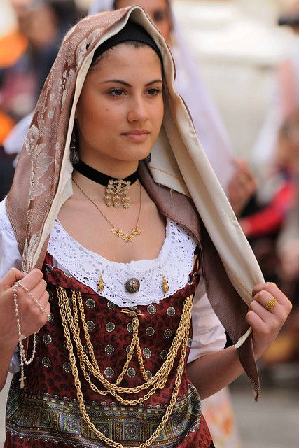 Il triangolo. 353 Sagra di Sant' Efisio, Cagliari.  Bellissima ragazza che indossa il costume di Sinnai, con splendidi gioielli e un fazzoletto che le incornicia perfettamente il viso.