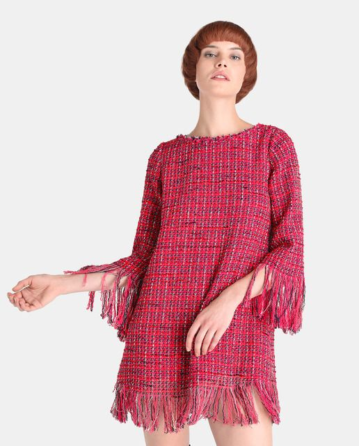Vestido corto de tweed con adorno de flecos. Tiene manga francesa, escote redondo y cierre de cremallera en la espalda.