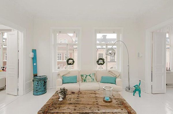 Loving this living room of turquoise and white.Some wooden pieces to balance the set up.