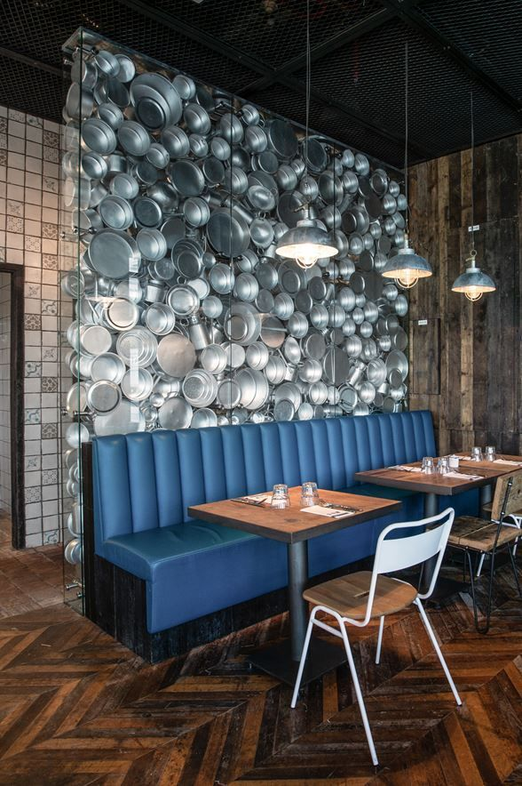 super cool restaurant installation featuring an entire fake wall of metal pots and pans the blue bench seating adds a touch of life and punch - Blue Restaurant Ideas