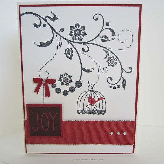 Holiday card with a floral flourish stamped in black ink, a festive bird stamped…