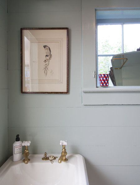 Bathroom - A simple white sink with brass fixtures below an intriguing portrait in a windowed bath. contemporary rustic