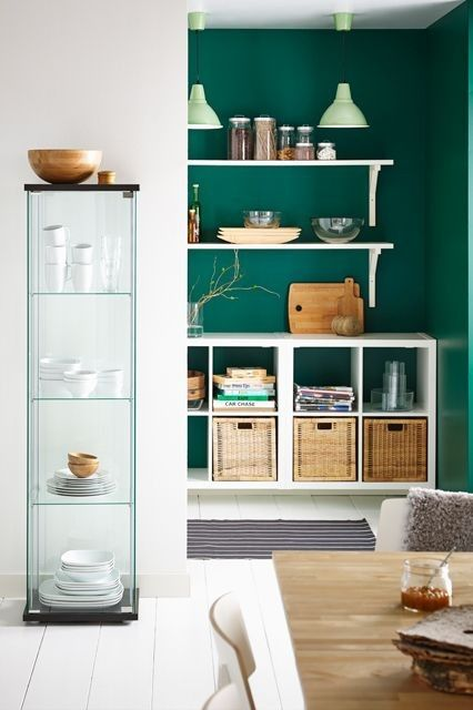 Paired with mint light fixtures, an emerald-meets-kelley green hue stuns on a kitchen wall
