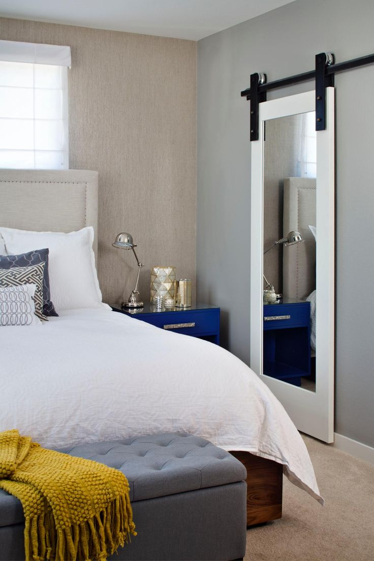 This neutral transitional bedroom is anything but boring thanks to the unexpected touch a barn-door mirror adds.