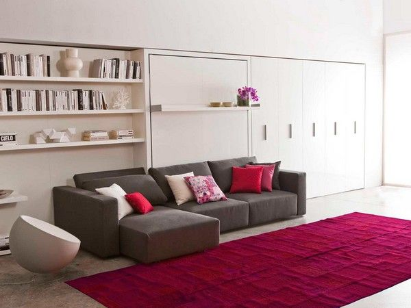 Modern sofa, with reclining back rest and storage. Integrated with wall modular shelving, transforms into a double bed always ready to use.