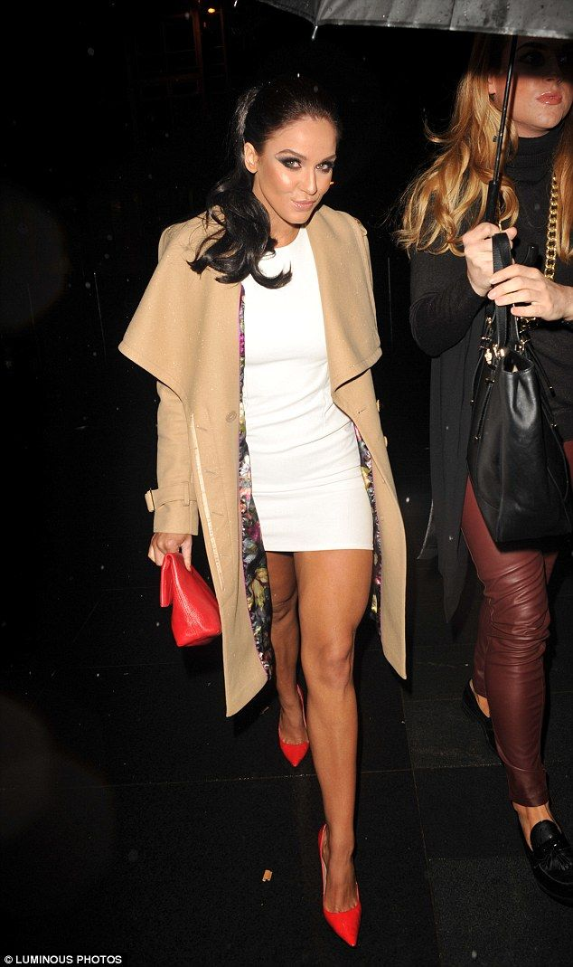 Chic in knee length camel coat, bright red heels and purse, and white mini dress