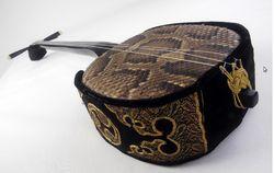 """SANSHIN Colección del Museo Azzarini El sanshin (三線, literalmente """"tres cuerdas"""") es un instrumento musical de Okinawa, precursor del shamisen japonés. Parecido a un laúd, consiste en un cuerpo cubierto de piel de serpiente, mango y tres cuerdas.  Desciende del sanxian chino, introducido alrededor del 1390 al archipiélago japonés de Okinawa, centro del antiguo reino de Ryukyu.  Como su antecesor, posee un mango largo y angosto, sin trastes. Este se continúa en una pica que atraviesa la caja…"""