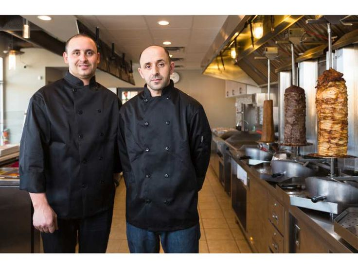 Alaa Abufarha, left, and his brother Izzo stand in their restaurant Jerusalem Shwarma