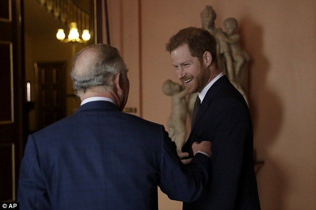 Prince Harry is  greeted by his father Prince Charles upon their arrival at a meeting in L...