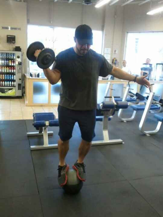 Scott squeezing out one arm curls while balancing on a medicine ball.