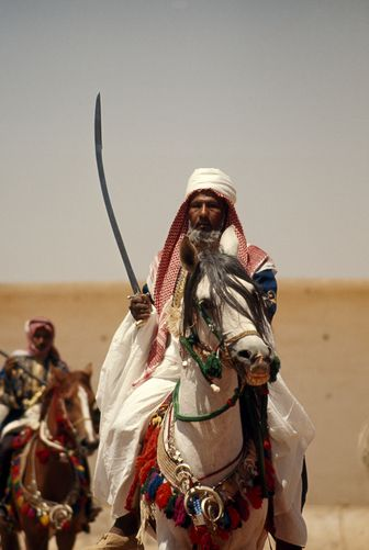 Bedouin with scimitar rides ornately garbed horse in royal horse show in Saudi Arabia by Thomas J. Abercrombie