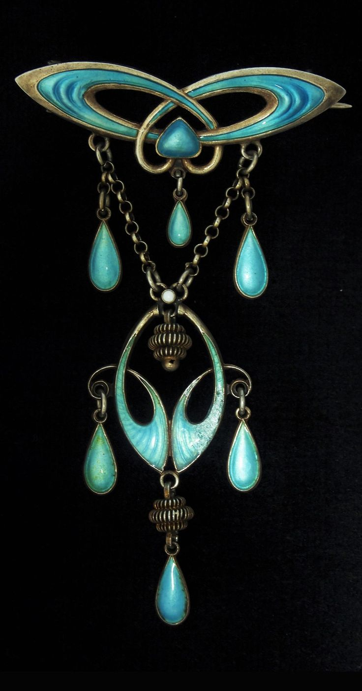 Marius Hammer - An Art Nouveau silver and blue enamelled festoon brooch, 1905-1910. Designed as an openwork wing-shaped bow from which is suspended an open enamelled oval on two short chains. Half a dozen small pear-shaped drops cleverly add a further lightness of look. Marked with the Marius Hammer maker's mark. #MariusHammer #ArtNouveau #brooch