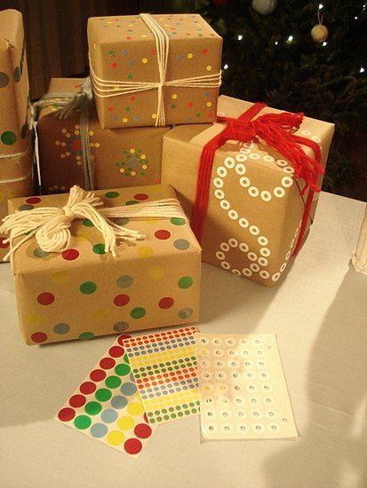 DIY: Wrapping With Craft Paper - Rip open a grocery store brown paper bag and wrap a gift so the unprinted side shows on the outside of the box. | Cover the package in office supply store stickers. | Tie it all up with wool yarn in festive colors.