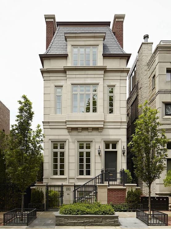 French limestone three story home boasts a black front door as well as a gray mansard roof.