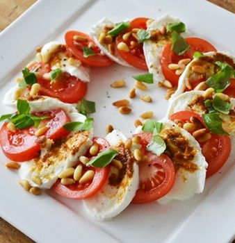 Salade Caprese -  •2 bolletjes mozzarella •3 tomaten •Handje verse basilicum •25 gram pijnboompitjes •Scheutje olijfolie •1 el pesto •Grove zwarte peper