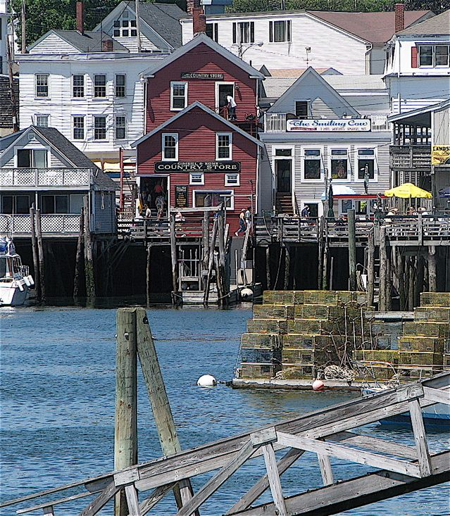 Boothbay Harbor's shops and restaurants hang over the harbor in Maine. Hilary Nangle photo.