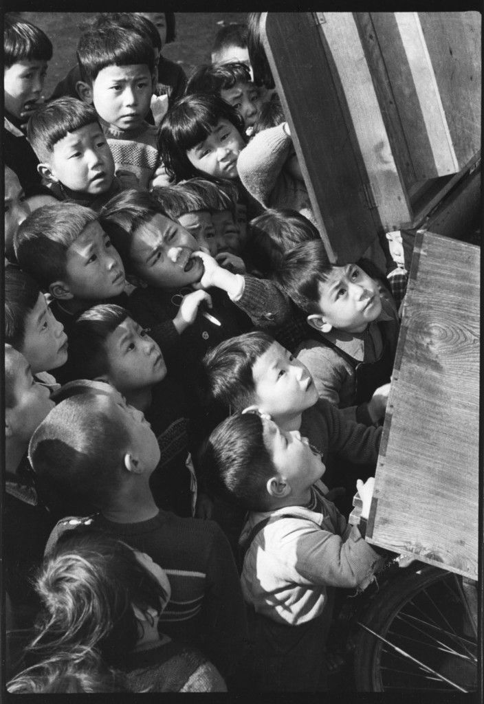 Children looking at a picture-card show Tokyo, 1953 by Ken Domon