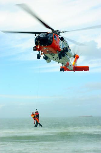 MOBILE, Ala. - The crew of a Coast Guard MH-60 Jayhawk helicopter from Coast Guard Aviation Training Center Mobile hoists Petty Officer 2nd Class Jonathan Foss and Luke Wiedeman as part of a search-and-rescue demonstration, Nov. 7, 2011. Crewmembers from ATC Mobile worked with the Mobile chapter of the Make-A-Wish Foundation to help Luke realize his dream of becoming a Coast Guard rescue swimmer. Petty Officer 3rd Class Stephen Lehmann