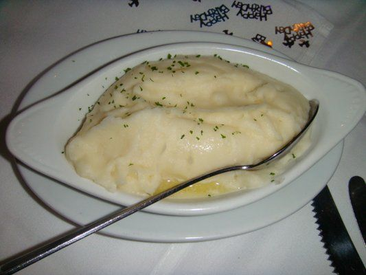 Ruth Chris Steakhouse Copycat Recipes: Garlic Mashed Potatoes  --- GARLIC MASHED POTATOES Ruth Chris Steak House Copycat Recipe  Serves 6-8  7 cups peeled and cubed baking potatoes 6 cloves garlic, peeled 1/2 cup low-fat milk 1/4 cup Parmesan cheese, grated 2 tablespoons butter 1/2 teaspoon salt 1/8 teaspoon pepper