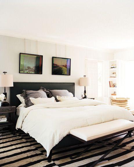 nicky kehoe contemporary masculine bedroom--velvet upholstered headboard, white linens, striped carpet, x bench, modern photography
