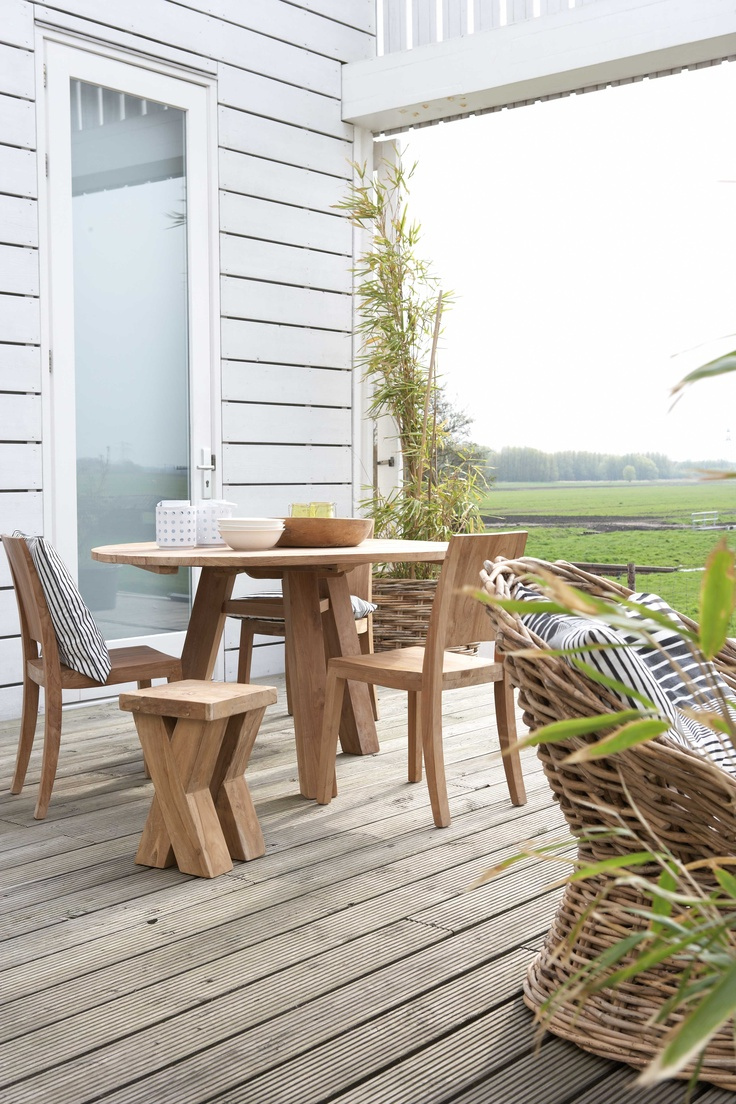 Teakhouten meubelen zijn uitermate geschikt om buiten te gebruiken. Hier worden verschillende stoelen en krukjes rondom de ronde tafel verzameld, zo is er voldoende plek voor iedereen!