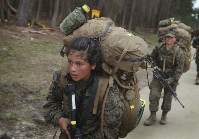 Marines finish a 10 kilometer training hike carrying 55 pound (25 kg) packs during Marine Combat Training (MCT) on February 22, 2013 at Camp Lejeune, North Carolina. Since 1988 all non-infantry enlisted male Marines have been required to complete 29 days of basic combat skills training at MCT after graduating from boot camp. MCT has been required for all enlisted female Marines since 1997. About six percent of enlisted Marines are female. (Photo by Scott Olson/AFP Photo)