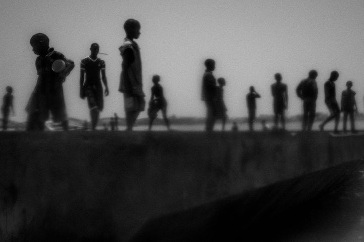 Runaway talibés stand on the banks of the Senegal river, in Saint Louis, north of Senegal by Mario Cruz