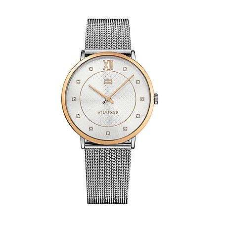 Tommy Hilfiger women's watch. Simple, elegant and bold, a crystal bedecked face adds shimmer to this boy-meets-girl watch. Designed with a silver mesh bracelet, the large face is detailed in gold with roman numerals at the twelve o'clock hour. <br>• Gold-plated stainless steel.<br>• 38mm case.<br>• Water-resistant up to 30 meters.<br>• 10-yr limited warranty.<br>• Imported.<br>