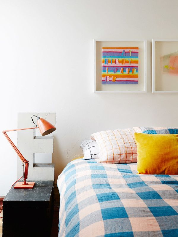 Kylie and Simon's colourful bedroom. Artworks by Jade Walsh, vintage planet lamp, all bed linen  from Kip and Co – 'we love their bold colours and patterns so much!' say Kylie. Black wooden box (used as side table) belonged to Simon's grandpa Noel, from the 50's. Photo – Annette O'Brien, production – Lucy Feagins / The Design Files.