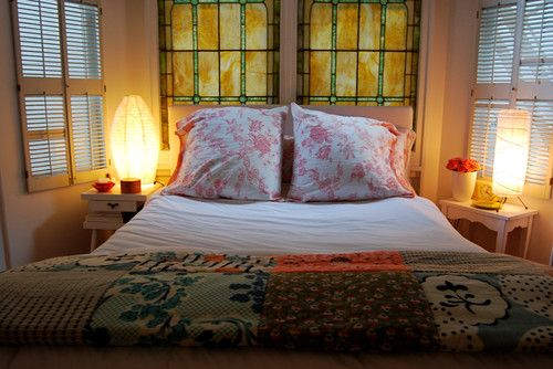 I'm not sure if those are windows with actual stained-glass in them, or if they are stained glass panels that are against the windows. But this look could definitely be created with stained glass panels or doors placed behind the bed. Very dramatic and beautiful.