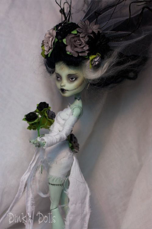 Monster High Frankie Stein basic repaint. Frankie's been given black lips and small black eyes, and stitched-up Glasgow smile-style scars. She's wearing a white dress made of strips of gauzy fabric, and her hair has been done up in the style of the Bride of Frankenstein. She's holding a bouquet of black and dusty purple roses, and there are matching flowers in her hair and veil. By SDink.