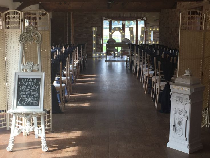 Stunning ceremony decor including navy vertical chair sashes, light up 5ft letters and white postal box all available from To Have & To Hire Events