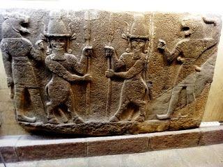 .Os personagens do centro são homens-touros, cujas faces estão voltadas de frente e seus corpos em perfil. Os homens com corpo de touro , chifres e orelhas, seguram lanças. Os homens touros são os deuses Kusarlldu e os homens leões os deuses Ugallu.
