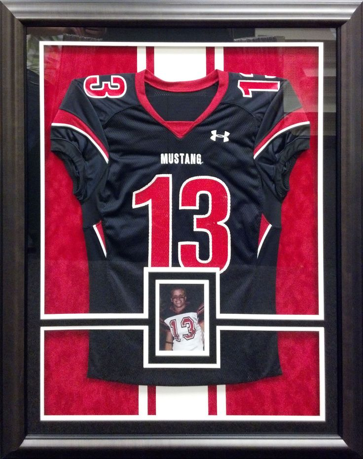 This football jersey is mounted on inlaid mats and is completely reversible. Our custom framing departments can mount jersey's and other sports memorabilia with industry approved methods.