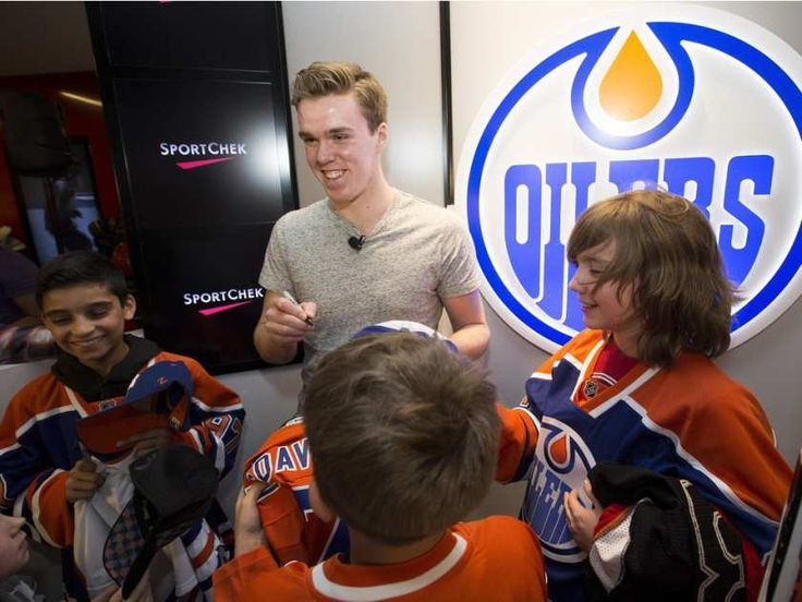 The Edmonton Oilers' Connor McDavid signs autographs for minor jockey players from the KC Renegades during a surprise visit with the team at the West Edmonton Mall Sport Chek in Edmonton on Monday, April 11, 2016.