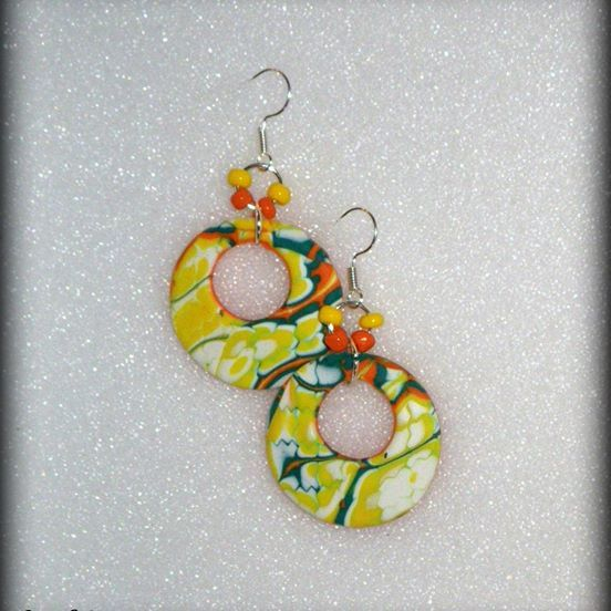 """Summer Sunny Days""! Dangle Disk #earrings. These lightweight earrings created by using the mokume cane technique with many layers of transitioning palettes. Featured colors are pure white, tiger orange and shamrock green. Supplemented with Czech seed beads. Modern geometric shape and elegant color palette make a simple yet original pair of earrings for perfect sunny day! About 4cm in diameter and 4,5 cm long with ear wear."