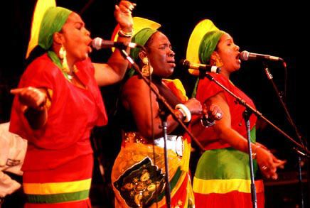"""The I Threes was a Jamaican reggae singing group that was formed in 1974 to support Bob Marley & The Wailers, after Peter Tosh and Bunny Wailer, the original Wailer backing vocals left the band.  From (l-r), singers; Judy Mowatt, Bob Marley's wife Rita Marley (not known to many is from Cuba), and far right Marcia Griiffiths. Their group name is derived from the belief that Rastafarian """"I and I"""" concept of the Godhead is within each person."""