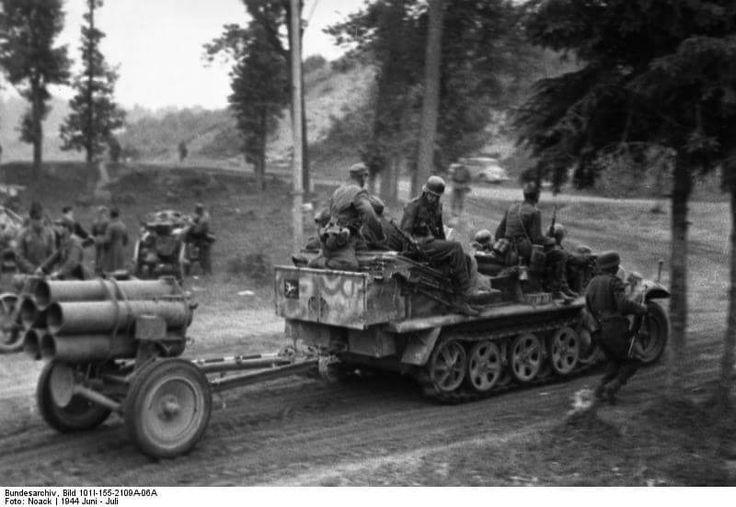 Halbkettenfahrzeug Sd. Kfz. 10, 1 t Zugkraftwagen, mit Nebelwerfer 42 des Werfer-Regiments 51 (4. deutsche Armee) auf Anhänger passiert ein Waldgebiet;