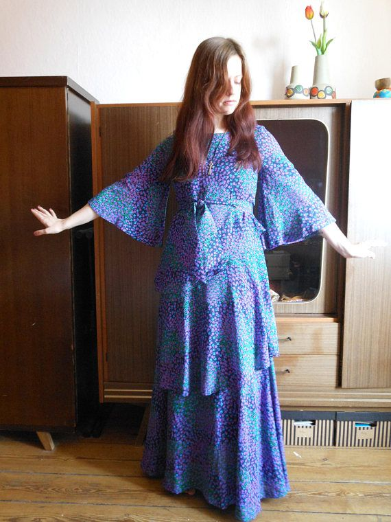 Beautiful stepped floral dress with flared sleeves from the 1970s. It has an undergarment and a fitting belt.  Vintage condition: Very good, no holes or flaws.  Label: Marketta. Made in Finland.  Fabric: 100% polyester.  Size: GB 10/ SF 36/ US 8.  Model on the photo: 173 cm, Size EUR 38.   Feel free to contact me for exact measurements or any questions! Please note that all my items offered here on etsy are vintage. That means the clothes are not new and are often varying in the siz...