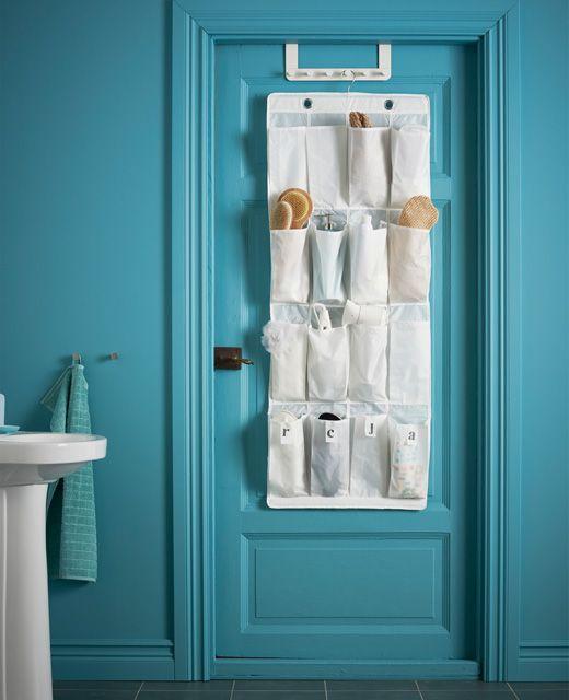 Eine Badezimmertür an dem eine Hängeaufbewahrung Bürsten, Haarsprays und anderen Utensilien ein neues Zuhause gibt.